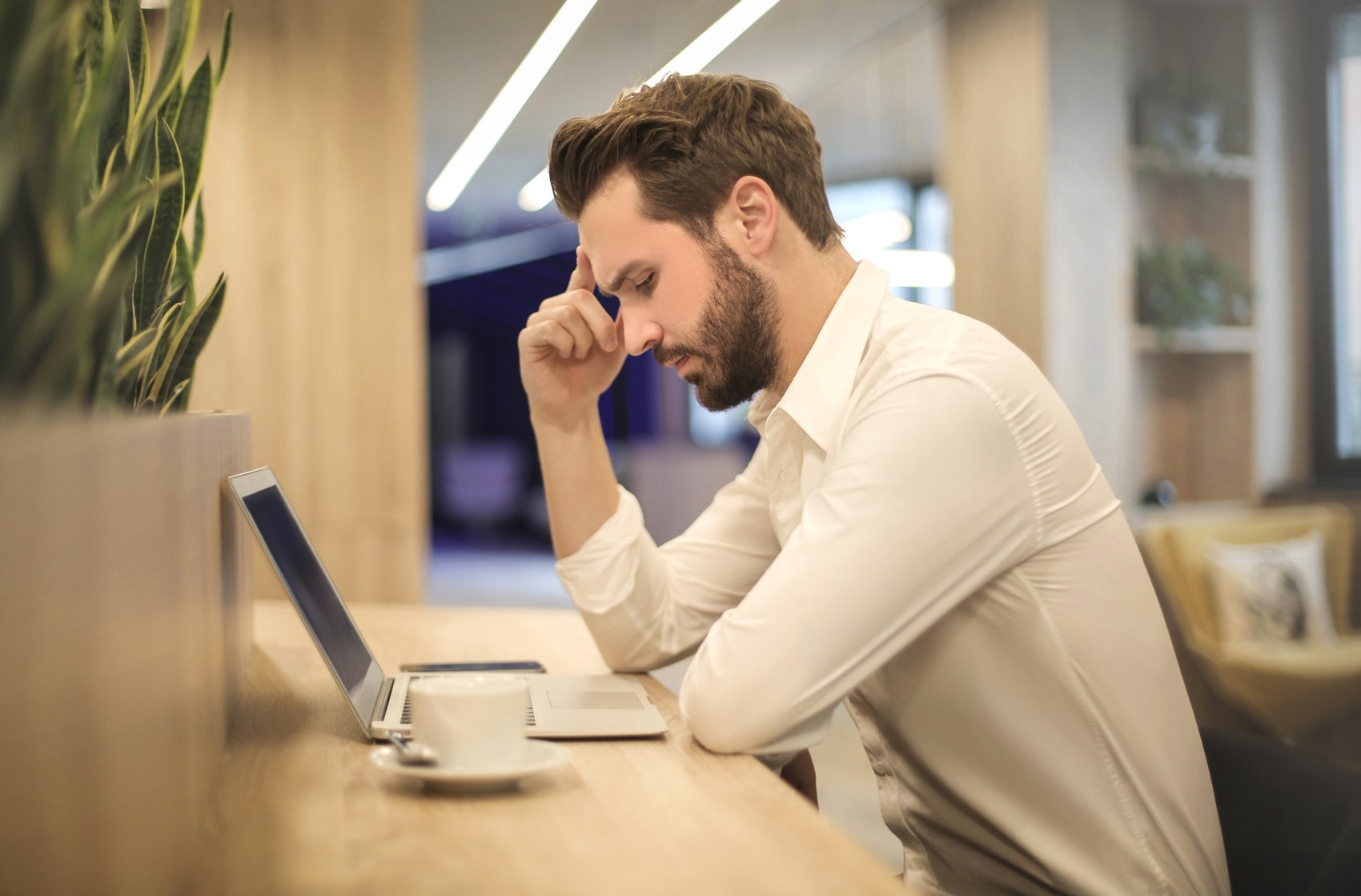Sales rep rubbing their head while looking at their computer