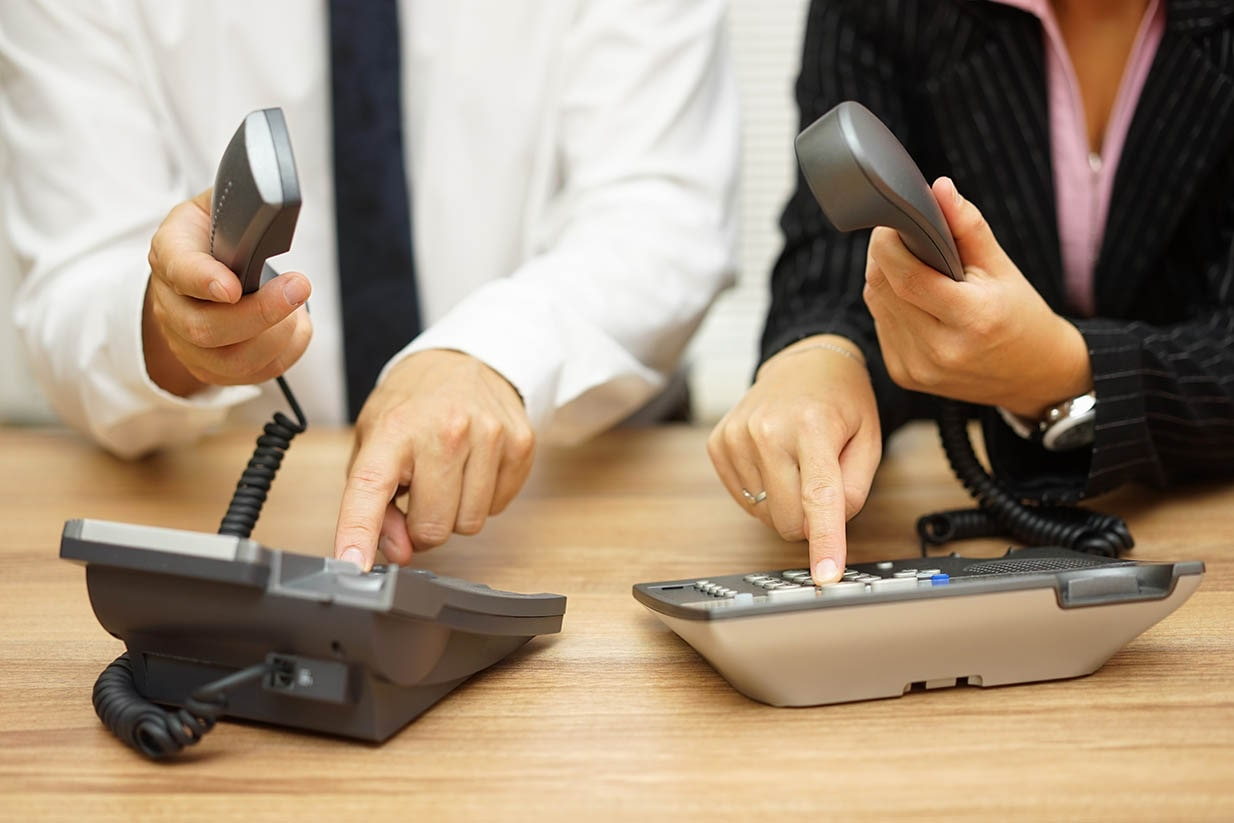 Two salespeople racing to dial on their desk phones