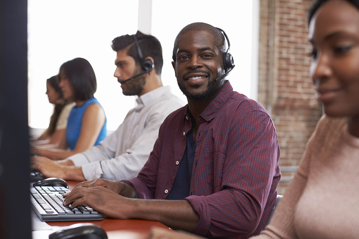 Row of sales reps working at their desks, one of whom is looking and smiling at the camera with their headset on