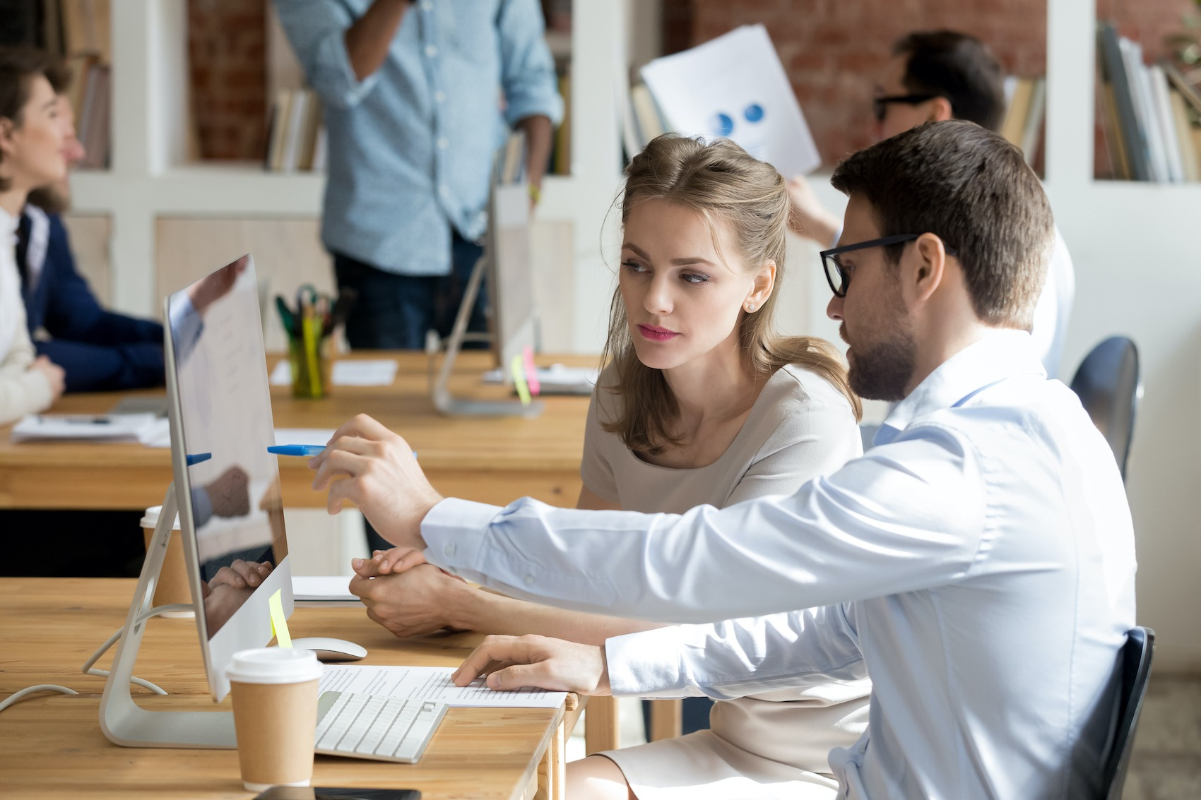 A manager explaining something on a computer screen during a sales coaching session with their team member