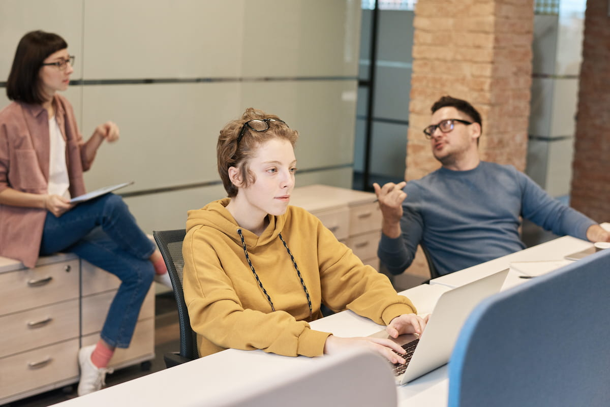 Salespeople working in an office, one is focusing on their work while the others chat